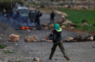 Palestyński chłopiec rzuca kamieniami w izraelskich żołnierzy podczas starć na Zachodnim Brzegu(zdjęcie: REUTERS)