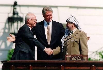 Działania i retoryka przywódców OWP pokazuje bez cienia wątpliwości, że nie spełnili żadnej z obietnic, jakie złożył przewodniczący OWP, Jaser Arafat, kiedy podpisał Umowy z Oslo w 1993 roku. Przywódcy OWP nadal nie uznają prawa Izraela do istnienia i nadal angażują się w terroryzm, gloryfikują terrorystów i wypłacają regularnie daninę ich rodzinom. Na zdjęciu: izraelski premier Icchak Rabin (po lewej), prezydent USA Bill Clinton (pośrodku) i Arafat przy podpisywaniu Umów z Oslo w Białym Domu w Waszyngtonie 13 września 1993 roku. (Vince Musi/The White House/Wikimedia Commons)