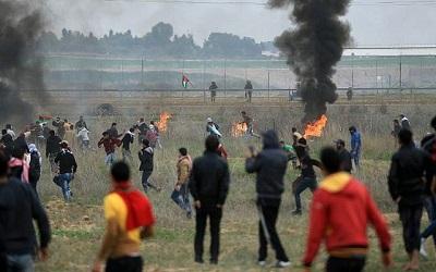 Palestyńczycy ścierają się z izraelskimi żołnierzami w pobliżu płotu granicznego na wschód od miasta Gaza 22 grudnia 2017 roku. (AFP/Mohammed Abed)