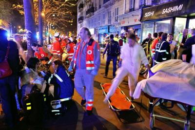 Po ewakuacji z Bataclan ludzie oczekują na ławce na dalszą pomoc. Paryż, sobota 14 listopada 2015. (AP Zdjęcie/Thibault Camus)