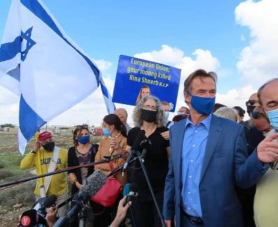 """Sven Kühn von Burgsdorff (w niebieskiej koszuli) oraz tajemniczy rzekomi europejscy dyplomaci. Z tyłu protestujący z plakatem głoszącym: """"Unio Europejska, twoje pieniądze zabiły Rinę Shnerb R.I.P."""""""