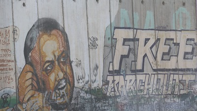 Podobizna Marwana Barghoutiego, terrorysty Fatahu, który odsiaduje dożywotni wyrok więzienia w izraelskim więzieniu za mordowanie izraelskich cywilów. Graffiti na murze bezpieczeństwa oddzielającym Zachodni Brzeg w pobliżu wsi Qalandiya, 6 maja 2016. Zdjęcie: Haytham Shtayeh/Flash90.