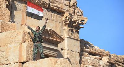 Syryjska flaga narodowa powiewa na tle ruin historycznego miasta Palmira w prowincji Homs w Syrii. 1 kwietnia 2016 r.