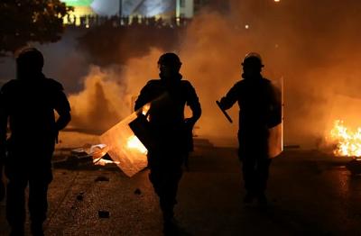 Libańskie policyjne oddziały prewencji w pobliżu ognisk rozpalonych w Bejrucie podczas protestu przeciwko spadkowi wartości waluty i narastającym problemom gospodarczym(zdjęcie: REUTERS/MOHAMED AZAKIR)