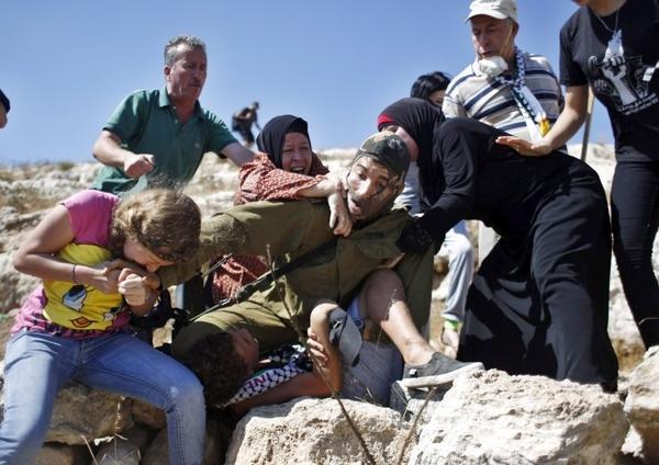 Zdjęcia uzbrojonego żołnierza izraelskiego, który nie użył broni, kiedy zajadle atakowały go palestyńskie kobiety i dzieci w Nebi Saleh, zdumiały wielu blogerów.