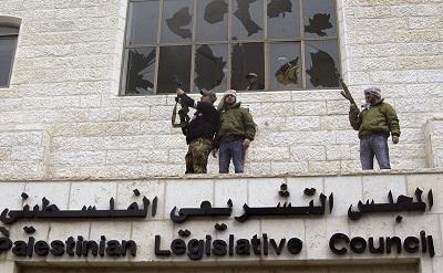 Na zdjęciu: Uzbrojeni członkowie palestyńskiego Fatahu okupują budynek Palestyńskiej Rady Ustawodawczej w Ramallah i strzelają w powietrze 28 stycznia 2006 r. w proteście przeciwko zwycięstwu Hamasu nad ich partią w wyborach, które odbyły się trzy dni wcześniej. (Zdjęcie: Zharan Hammad/Getty Images)