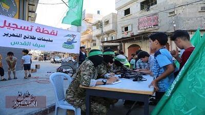 """Hamas wezwał Palestyńczyków w Strefie Gazy do rejestrowania swoich synów na letnie obozy wojskowe. """"Celem obozów jest rozpalenie płomieni dżihadu w pokoleniu wyzwolenia, wpojenie islamskich wartości i przygotowanie następnej zwycięskiej armii do wyzwolenia Palestyny"""" – oznajmił Hamas. Na zdjęciu:Stoisko rejestracyjne dla """"Pionierów wyzwolenia – obozów Miecz Jerozolimy"""" (Źródło: T.me/Tlae3Camps, 17 czerwca 2021)"""
