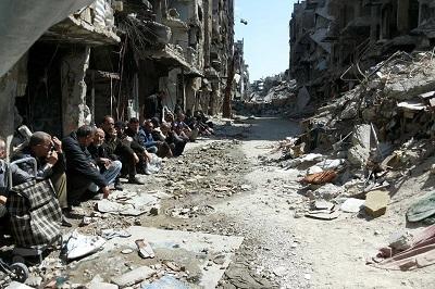 Na zdjęciu: Palestyńczycy siedzą w ruinach obozu uchodźców Jarmouk w Syrii dostały się (Źródło: UNRWA)