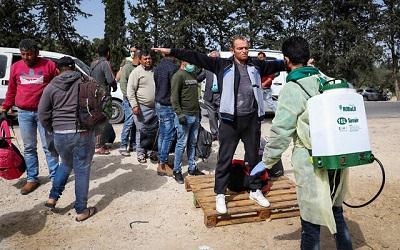 Sfabrykowanie opowieści o chorych pracownikach szmuglowanych w kanałach do odprowadzania wody i o Żydach, którzy chodzą i plują, są częścią nowej palestyńskiej kampanii podżegania przeciwko Izraelowi z koronawirusem jako pretekstem. Główne przesłanie kampanii: Izrael (lub, żeby mówić ściślej, Żydzi) umyślnie szerzą koronawirusy wśród Palestyńczyków. Na zdjęciu: Pracownik ministerstwa zdrowia Autonomii Palestyńskiej spryskuje środkiem dezynfekującym robotników, którzy wracają z Izraela przez przejście Tarkumiah, 27 marca, 2020. (Wisam Hashlamoun/Flash90)