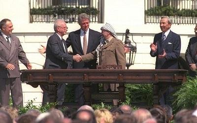Bill Clinton patrzy jak Icchak Rabin i Jaser Arafat podają sobie ręce podczas historycznego podpisywania Umów z Oslo, 13 września 1993 roku. (GPO)