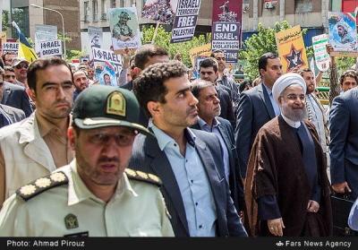 """Prezydent irański Hassan Rohani w marszu z okazji Dnia Kuds w Teheranie. Plakaty z tyłu mają swastykę wplecioną w słowo """"Izrael"""" (Fars, Iran, 1 lipca 2016)"""