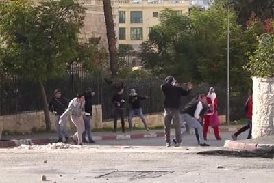 Muzułmanie palestyńscy w okolicach Betlejem, wśród nich mężczyźni przebrani za św. Mikołajów, ciskają kamieniami w żołnierzy izraelskich, krzycząc \