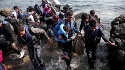 Uchodźcy syryjscy lądują na wybrzeżu greckiej wyspy Lesbos w nadmuchiwanym pontonie, którym przepłynęli Morze Egejskie z Turcji, 3 września 2015. (AFP/Angelos Tzortzinis)