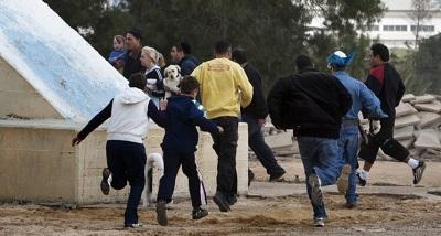 Izraelczycy biegną do schronu podczas palestyńskiego ataku rakietowego na Beer Szewę 23 marca 2011 r. Zdjęcie: Menahem Kahana/AFP via Getty Images.