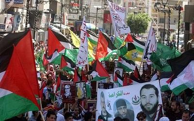Przez kilka minionych tygodni tysiące Palestyńczyków w Jerozolimie i na Zachodnim Brzegu demonstrowały, by poprzeć Hamas, szczególnie po tym, jak wystrzelił tysiące rakiet i pocisków na Izrael. Na zdjęciu: Tłum Arabów wymachuje flagami Hamasu w Ramallah. (Zdjęcie:Issam Rimawi/Flash 90)