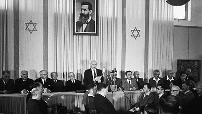 Izraelski ojciec-założyciel i pierwszy premier, David Ben-Gurion, deklaruje niepodległość pod dużym portretem Theodora Herzla, założyciela nowoczesnego syjonizmu. Zdjęcie: Wikimedia Commons.