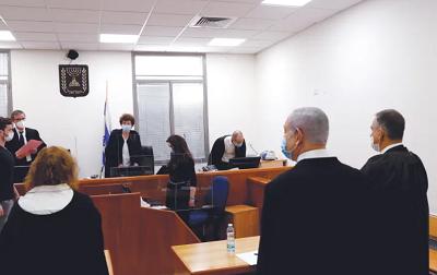 Premier Benjamin Netanjahu, w maseczce, stoi na sali sądowej okręgowego sądu w Jerozolimie podczas otwarcia jego procesu 24 maja. (zdjęcie: RONEN ZVULUN / REUTERS