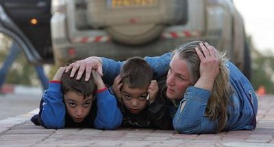 Izraelska matka chroni swoje dzieci podczas alarmu rakietowego w kibucu Kfar Aza w południowym Izraelu, 7 stycznia 2009 (Zdjęcie: JACK GUEZ/AFP via Getty Images)
